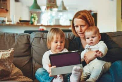 A mother with two kids are looking at a tablet